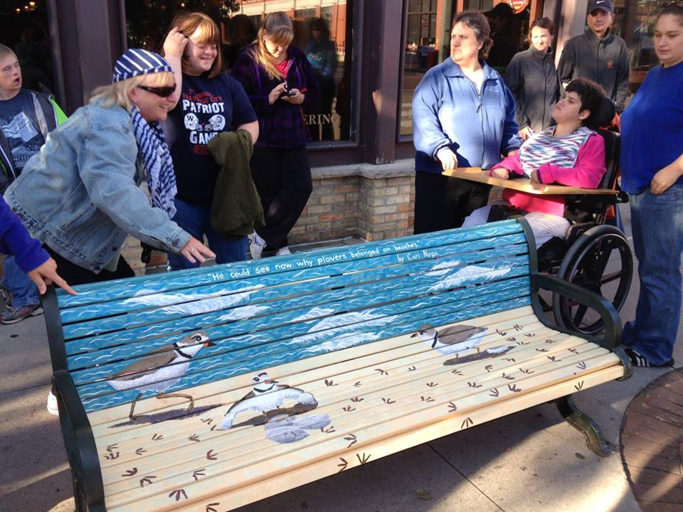 Teacher Lorraine Laird, in sunglasses, unveils the bench to her students.